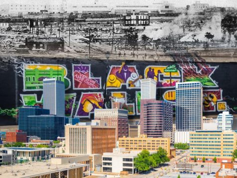 """Three images overlaid. In the background, in place of the sky, is a black and white image of Tulsa being destroyed. On the horizon line is an overlaid image of a mural from present-day Tulsa with the text """"Black Wall Street,"""" a homage to the city"""